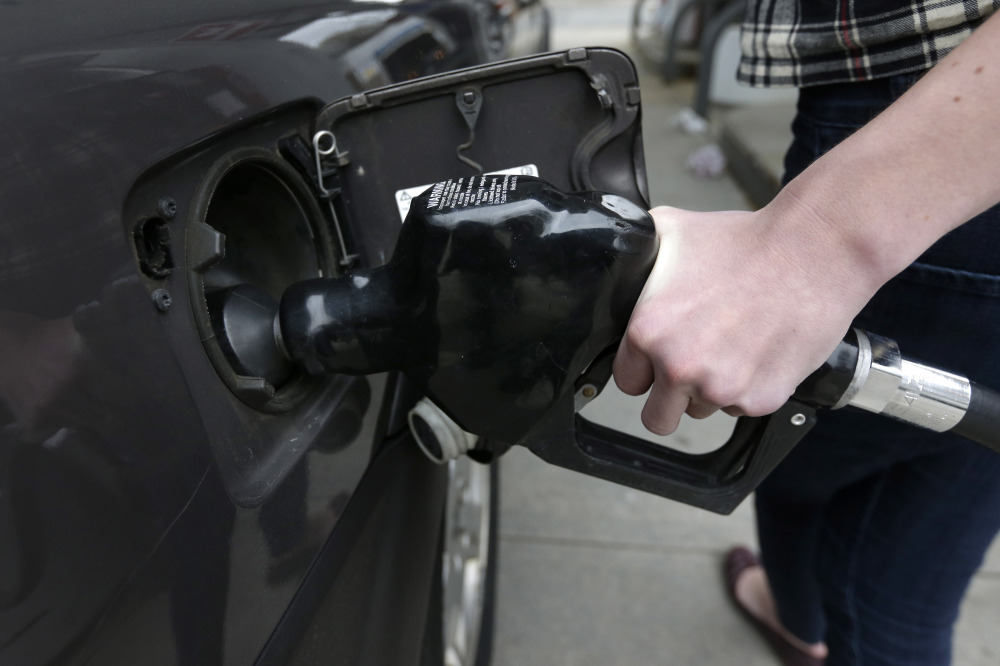 A customer fills her car with fuel at a gas station in Brookline, Mass. Gasoline prices are falling along with oil prices this summer because concerns of global supply disruptions have subsided somewhat despite continued violence in the Middle East.