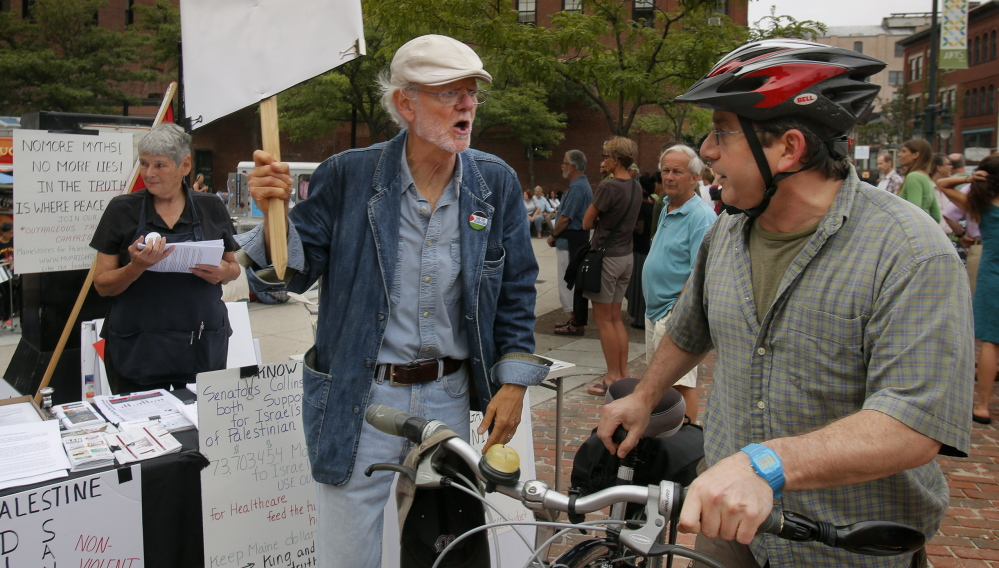 Bob Schaible, left, was protesting in support of Palestinians on Friday night when Natan Khan was riding through Congress Square with his two sons and felt compelled to stop and defend Israel's actions in the Gaza Strip.