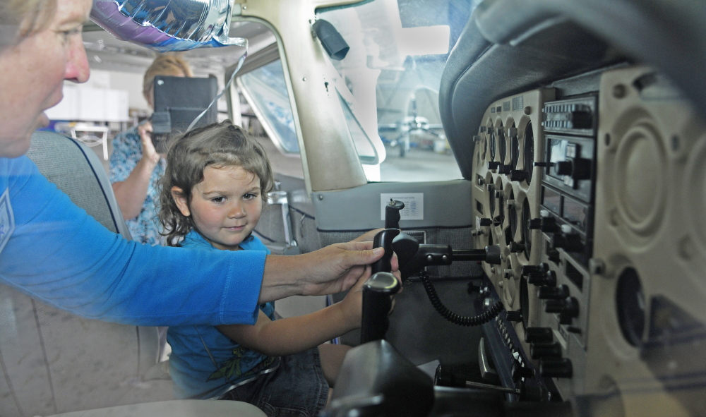 Lisa Reece, president of Maine Aeronautics, left, shows Karen Munzing, 3, the controls of a plane during an Amelia Earhart event Saturday at the Augusta State Airport.