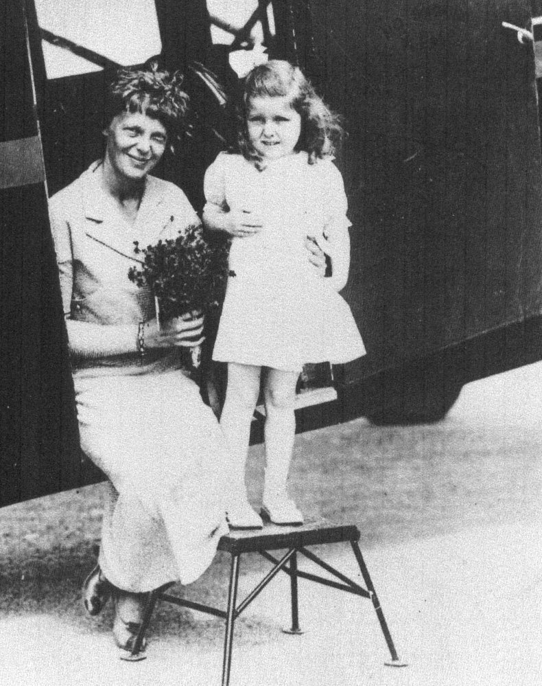 Amelia Earhart receives flowers from 5-year old Gladys Chase of Augusta on Aug. 14, 1934, at  the Augusta airport. The two were photographed in the doorway of a Boston & Maine Airways Stinson plane.