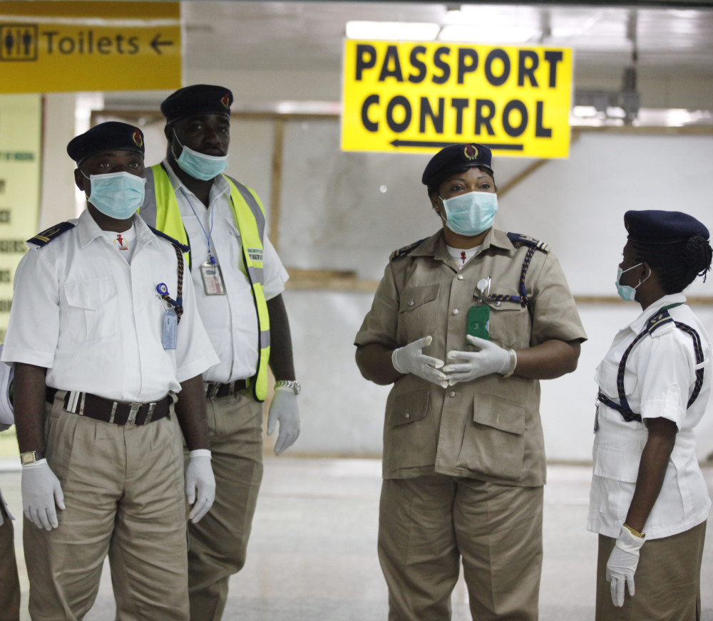 Nigerian health officials wait to screen passengers at Murtala Muhammed International Airport in Lagos, Nigeria, on Monday. The confirmation of a second Ebola case in Africa's most populous country is seen as an alarming setback.