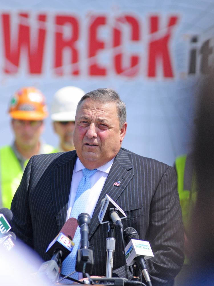 """Gov. Paul LePage stands in front of a truck with the words """"One text or call could wreck it all,"""" as he talks about distracted driving on Tuesday during a news conference in the parking lot outside State Police headquarters in Augusta."""