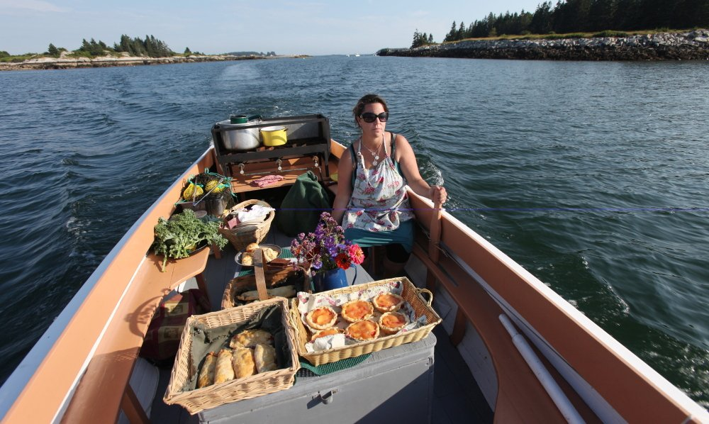 Reilly Harvey guides her boat Mainstay out into the harbor between Dix Island and High Island. Harvey runs Mainstay Provisions, selling lobster dinners and baked goods to boaters from her 1960s North Haven launch.