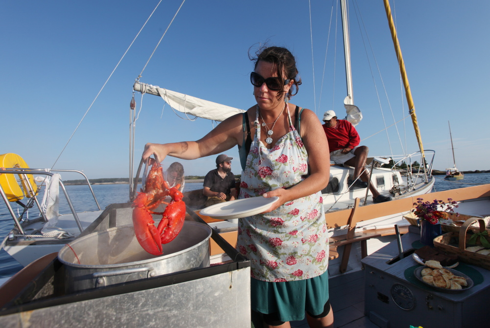 Reilly Harvey pulls a cooked lobster from a pot on board her boat Mainstay in the harbor between Dix Island and High Island.