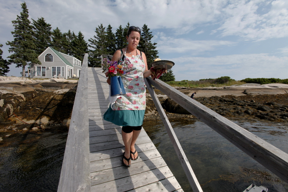 ANDREWS ISLAND, ME Ð JULY 26: Reilly Harvey carries flowers and biscuits down the ramp from her house to her boat Saturday, July 26, 2014 on Andrews Island, Maine. Harvey runs Mainstay Provisions, selling lobster dinners, and baked good to boaters from her 1960s North Haven launch. (Photo by Joel Page/Staff Photographer)