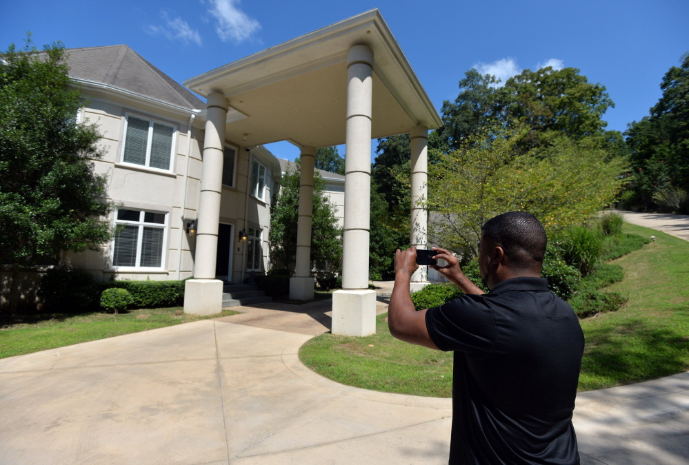 """Craig Craft takes a photo of the $1.7 million house he """"manages"""" through a program called Showhomes of Atlanta. He gives the otherwise empty and impersonal estate a warm, inoffensive, lived-in look. In return, he gets to """"live a life of luxury,"""" while splitting the $1,200 monthly rent with a roommate."""