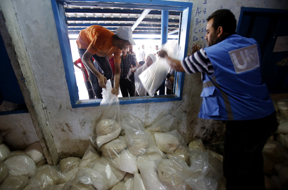 Palestinians crowd a window for food aid at a United Nations distribution center in the Shati refugee camp in Gaza City on Wednesday.