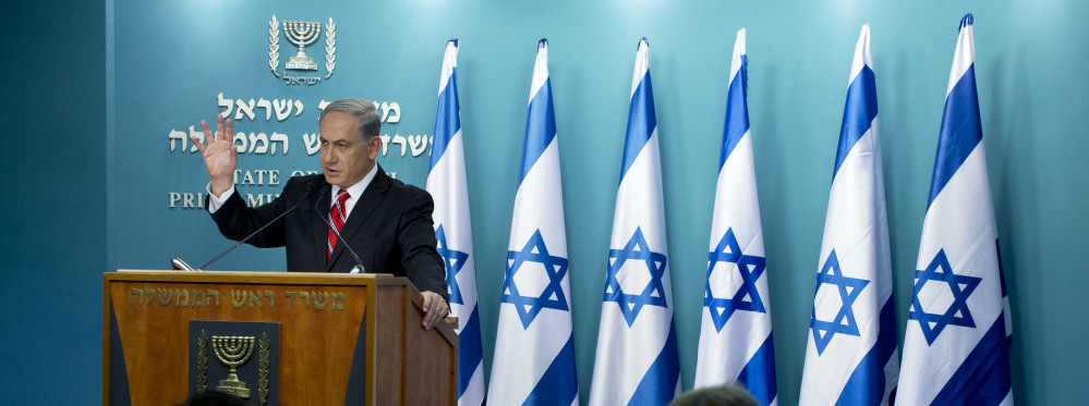 """Israeli Prime Minister Benjamin Netanyahu speaks at a news conference in Jerusalem on Wednesday. He defended Israel's intense bombardment of Gaza, saying that despite the high civilian death toll it was a """"justified"""" and """"proportionate"""" response to Hamas attacks."""