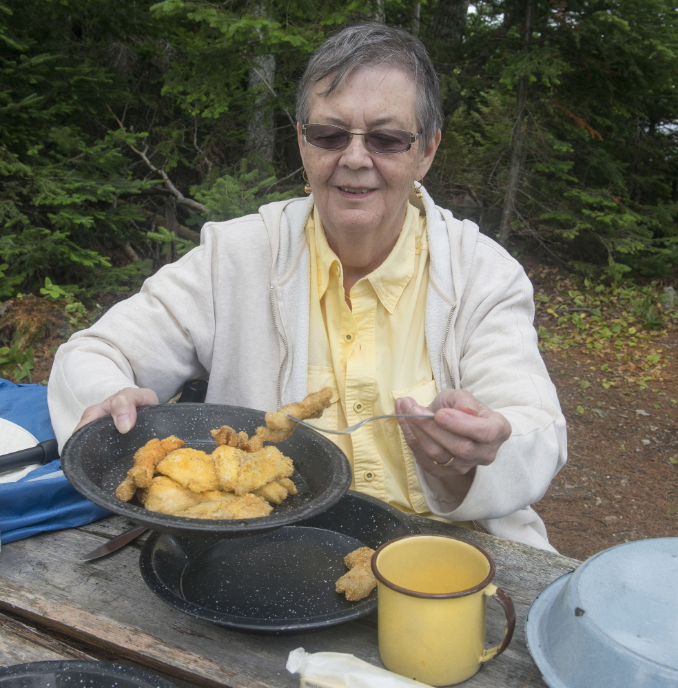 Mary Anne Kadzielawski of Morrisville, N.C., helps herself to freshly fried fish filets prepared by Maine guide Lance Wheaton at a traditional guide's shore lunch.
