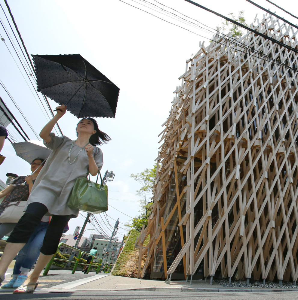 "Pedestrians pass Sunny Hills, known as the ""Pineapple House,"" designed by Japanese architect Kengo Kuma."
