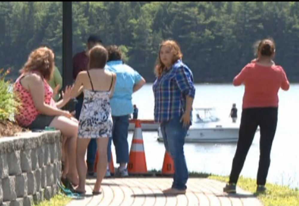 Spectators gather on shore as rescuers search the Penobscot River after a boy fell in and his grandfather jumped in to try to save him Friday morning.