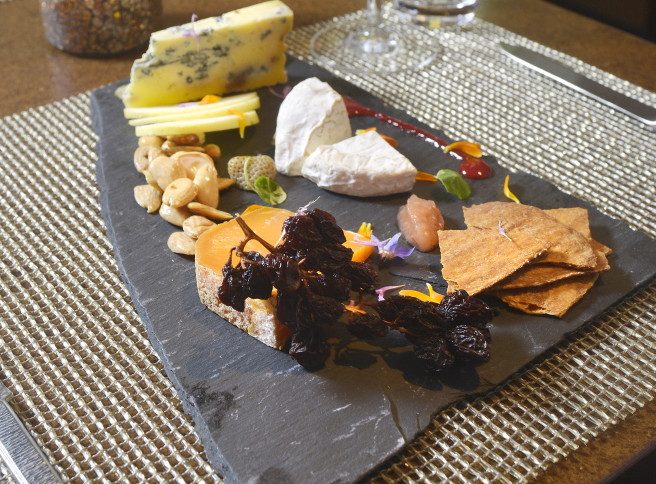 The awe-inspiring portal to the former Chestnut Street Church, now the entrance to Grace. At right, a cheese plate at Grace features Medalion (Maine), Mimolette (France) Asher Blue (Georgia) along with Marcona almonds, raisins-on-the-vine, pickled green strawberries, and housemade crackers. John Ewing/Staff Photographer