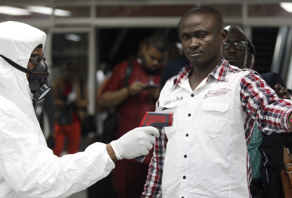 A Nigerian official uses a thermometer on a worker at the airport arrivals hall in Lagos. Ebola emerged in Guinea in March and has spread to Sierra Leone, Liberia and Nigeria.