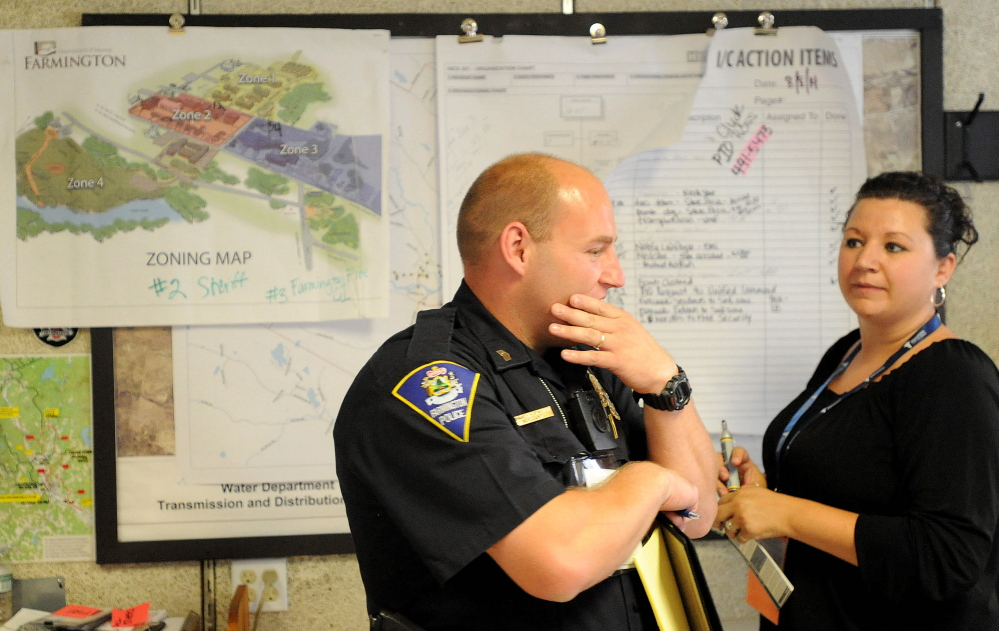 Farmington Police Sgt. Edward Hastings, left, coordinates with an official from the incident command center at the Farmington Fire Department on Friday.