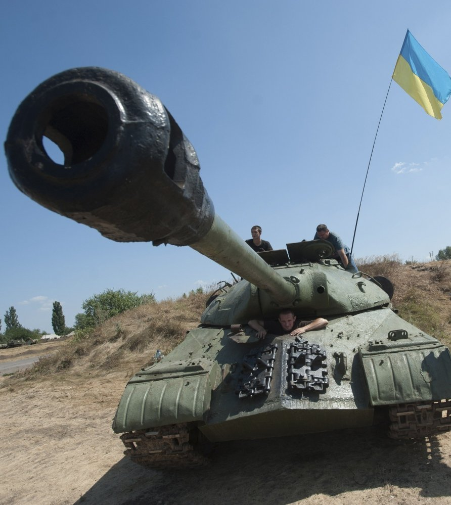 Ukrainian government soldiers drive their tank with a Ukrainian national flag in Donetsk region, eastern Ukraine, Saturday.