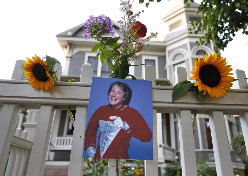 A photo of the late actor Robin Williams as Mork from Ork hangs with flowers left by people paying their respects, in Boulder, Colo., Monday.