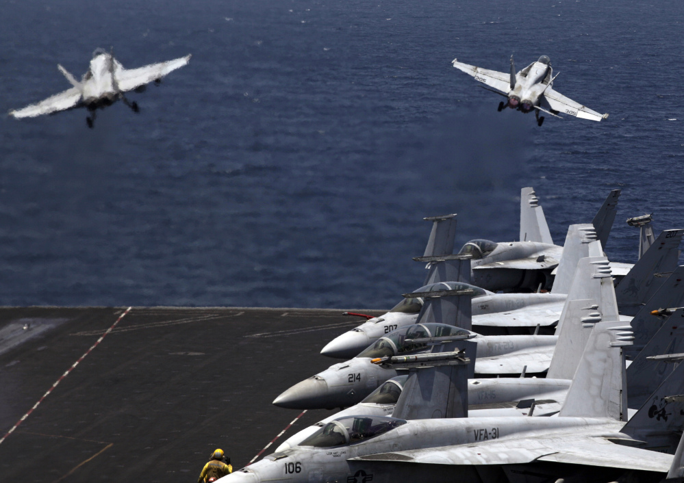 U.S. F/A-18 fighter jets take off for a mission in Iraq from the flight deck of the U.S. Navy aircraft carrier USS George H.W. Bush, in the Persian Gulf on Monday.
