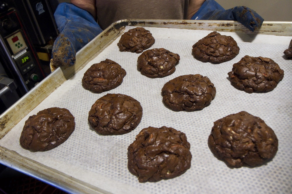 Chunky chocolate rye cookies, made with Maine-grown rye, are put into a rack to cool at Standard Baking Co. in Portland.