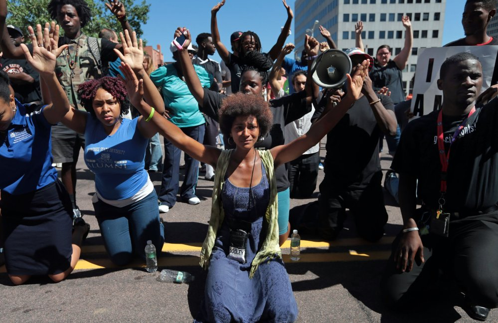 Protesters drop to their knees and raise their arms during a rally in Clayton, Mo., on Tuesday for Michael Brown Jr., who was shot and killed by a police officer Saturday.