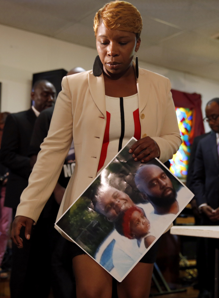 Lesley McSpadden, the mother of 18-year-old Michael Brown, holds a photo of her son, seen at top left, as she attends a news conference Monday in Jennings, Mo. Michael Brown was shot and killed in a confrontation with police in the St. Louis suburb of Ferguson, Mo., on Saturday.