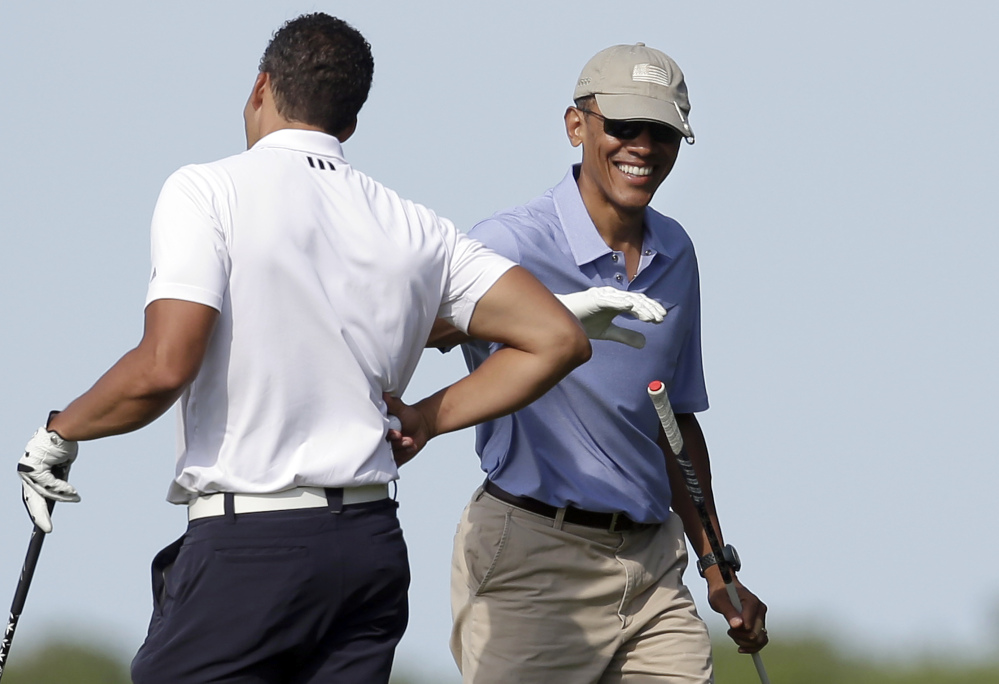 President Barack Obama, right, smiles as he gives a pat on the arm to Cyrus Walker, left, cousin of White House senior adviser Valerie Jarrett, while golfing at Vineyard Golf Club, Tuesday, in Edgartown, Mass., on the island of Martha's Vineyard.