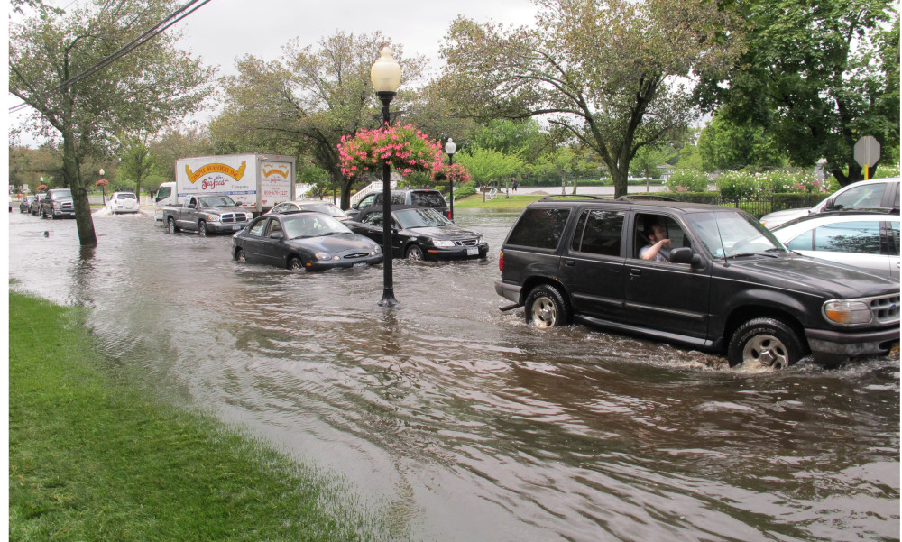 Vehicles attempt to maneuver down a flooded Montauk Highway in Babylon,  N.Y., Wednesday. The Associated Press