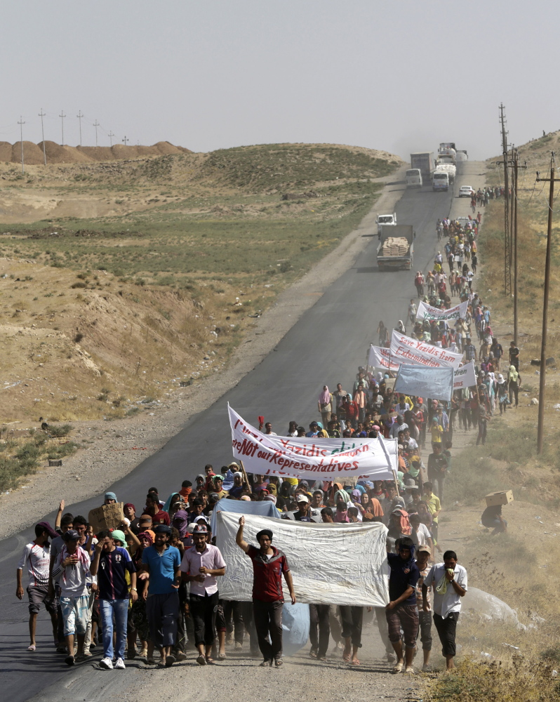 Displaced people of the minority Yazidi sect, who fled the violence in the Iraqi town of Sinjar, take part in a demonstration Wednesday at the Iraqi-Syrian border crossing in Fishkhabour, Dohuk province, Iraq.