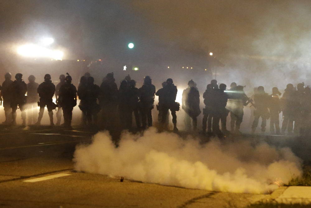 "Police advance through smoke Wednesday night in Ferguson, Mo. ""An undertow (of racial unrest) has bubbled to the surface,"" said Police Chief Thomas Jackson."