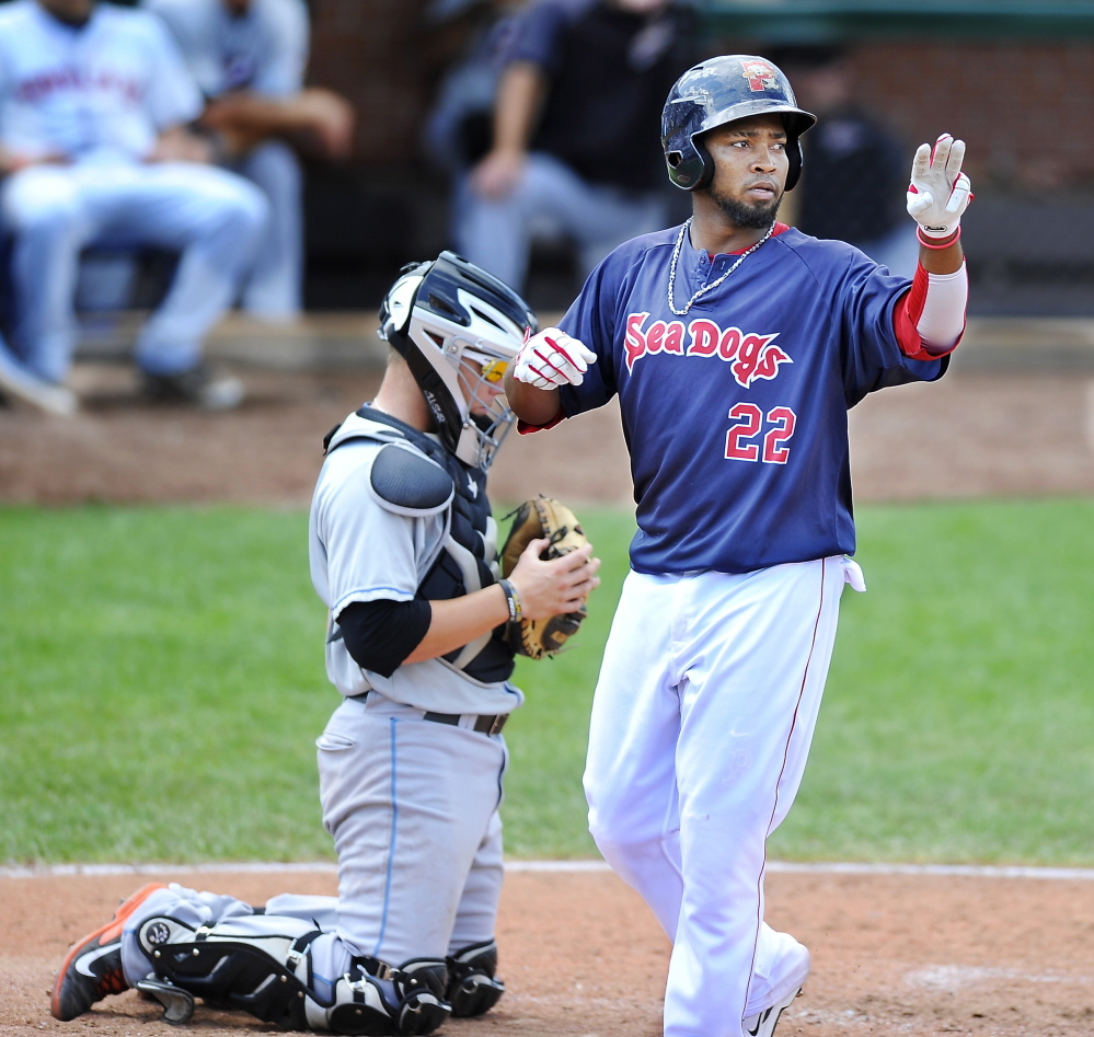 Portland's Keury De La Cruz gives the sign while crossing the plate after hitting a home run. Press Herald File Photo/Gordon Chibroski