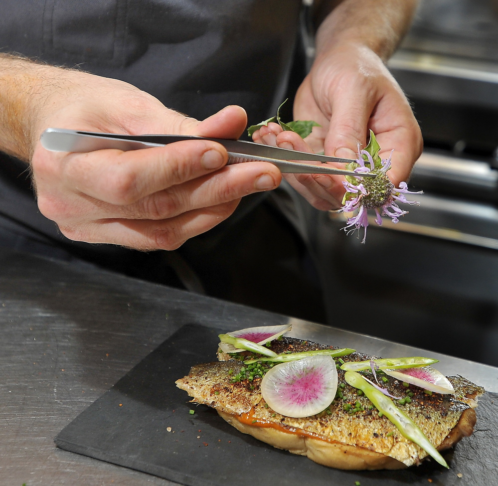 Chris Gould of Central Provisions garnishes his grilled Maine sardine crostini with sliced radish and flower petals and leaves.