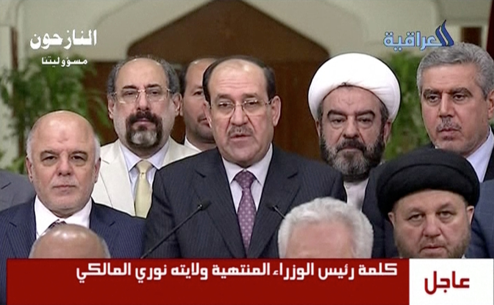In this image taken from video Thursday, Nouri al-Maliki, Iraq's prime minister for the past eight years, relinquishes his post to fellow Dawa Party member Haider al-Abadi.