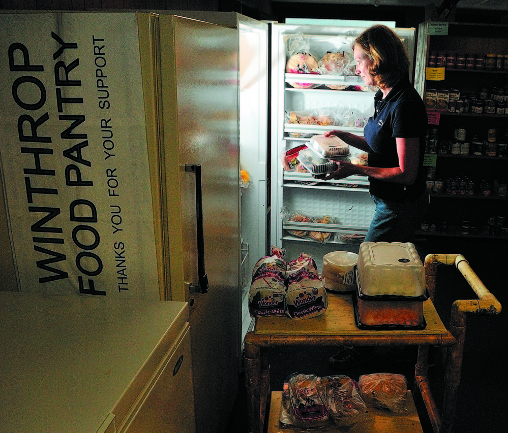 JoEllen Cottrell takes baked goods from the freezer as she and other volunteers set up the Winthrop Food Pantry in June 2011. A fundraiser Saturday will help raise money for growing need at the pantry.