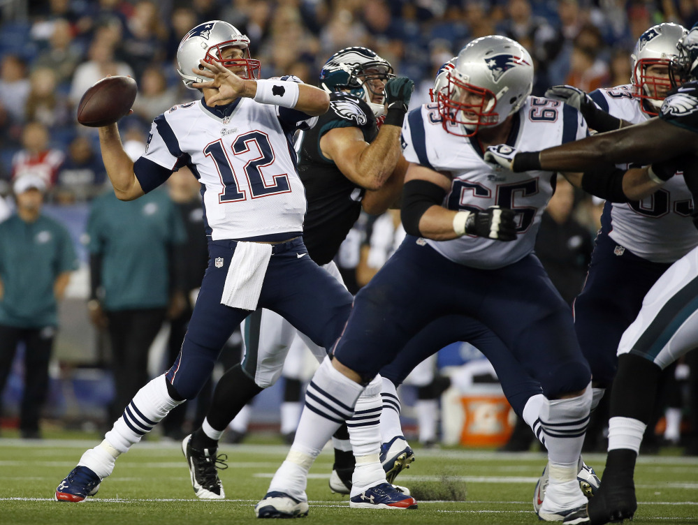 New England Patriots quarterback Tom Brady passes against the Philadelphia Eagles behind a block by tackle Jordan Devey (65) in the first quarter Friday night in Foxborough.