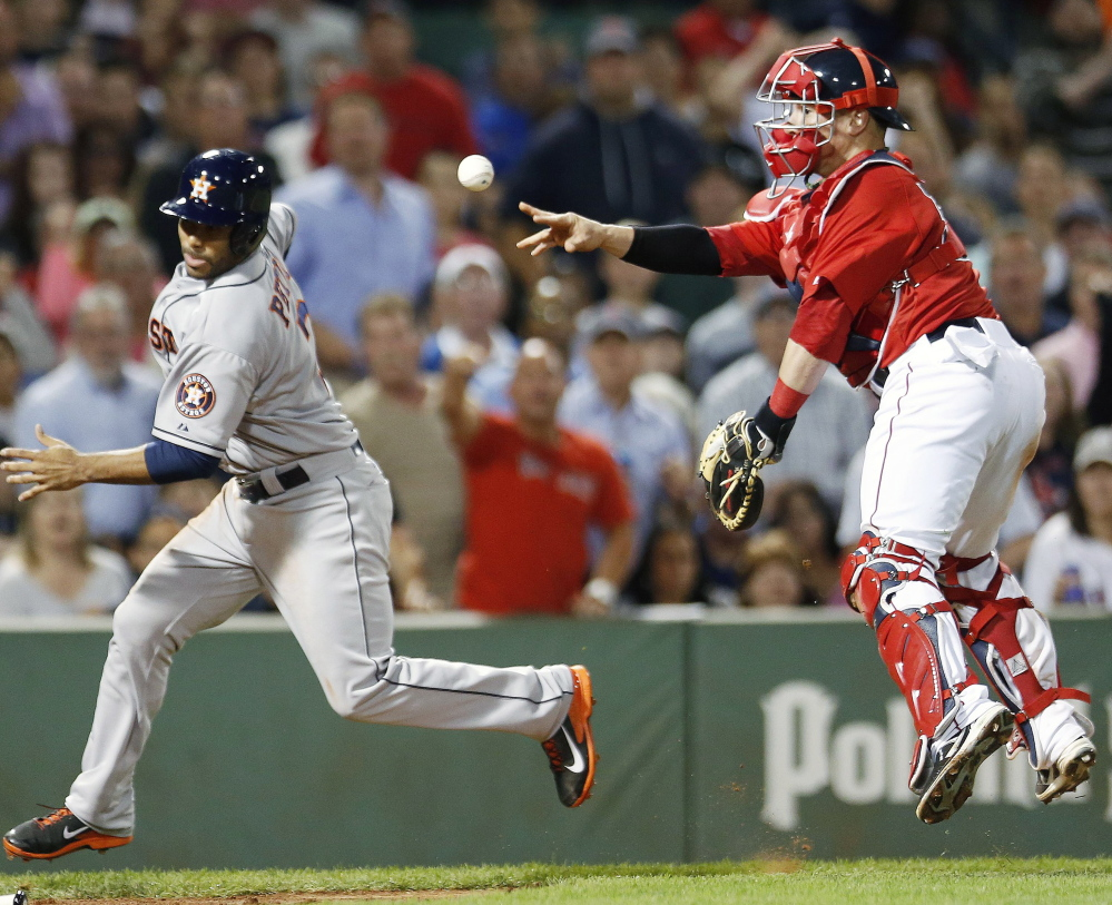 Gregorio Petit of the Astros avoids Red Sox catcher Christian Vazquez, whose throw to pitcher Burke Badenhop at the plate wasn't in time to prevent Petit from scoring the tying run in the eighth inning Friday night.