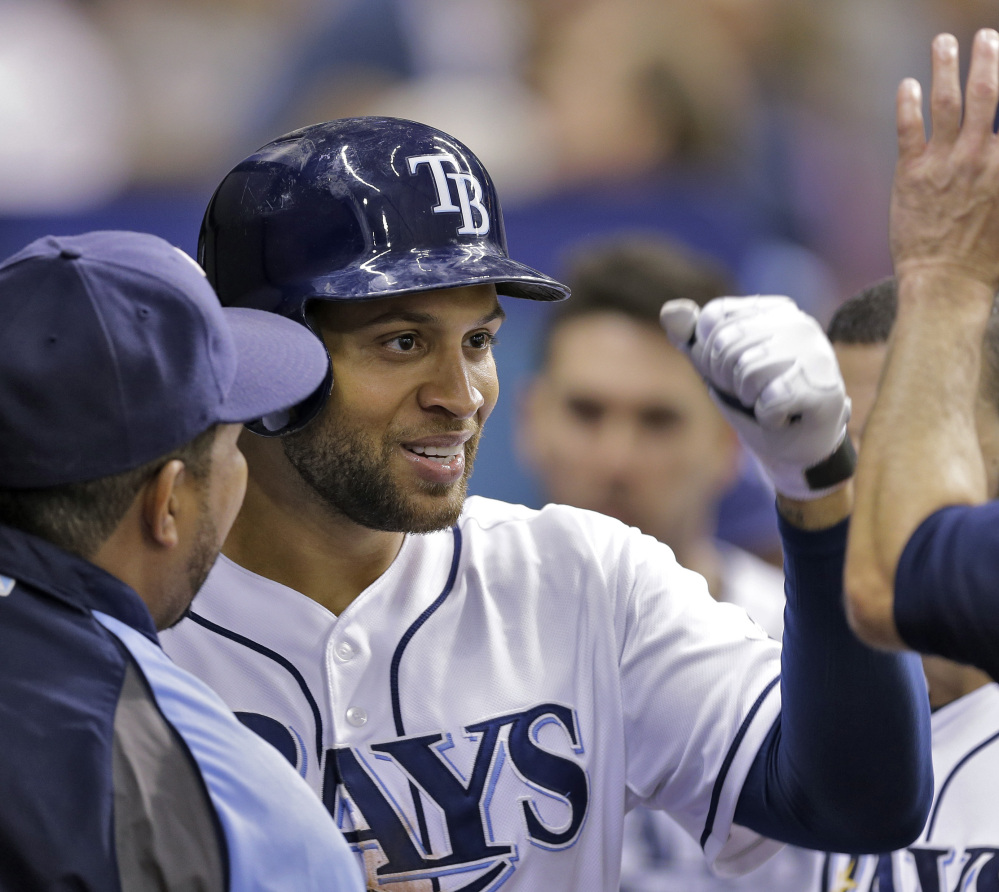 Tampa Bay Rays' James Loney high-fives teammates after hitting a home run off New York Yankees relief pitcher Esmil Rogers during Friday's victory.