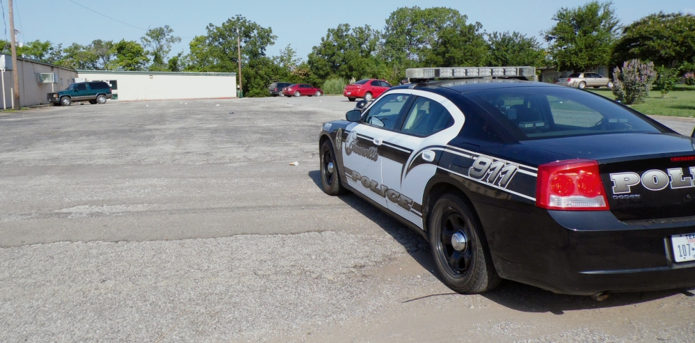 A police vehicle sits outside a North Texas roller skating rink in Grainville, Texas, on Saturday. Two people were stabbed to death and several were wounded in a fight early Saturday.