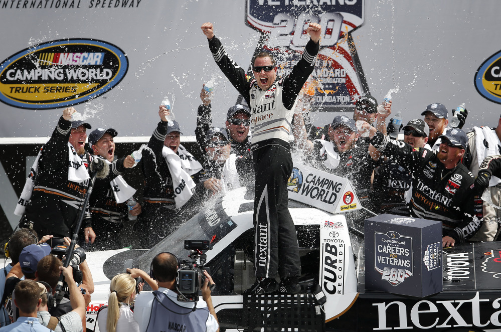 Driver Johnny Sauter, center, celebrates in Victory Lane after winning the NASCAR Camping World truck series auto race at Michigan International Speedway in Brooklyn, Mich., on Saturday