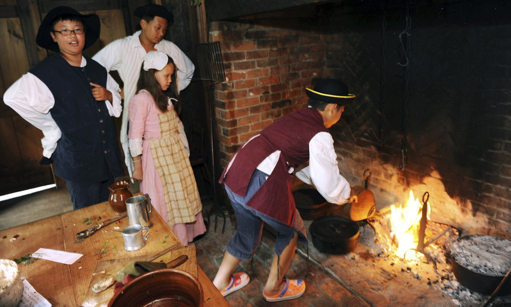 International students learn how to bake a blueberry pie in an open hearth with an artist from the Pocumtuck Valley Memorial Association at the Indian House Children's Museum in Old Deerfield, Mass. The learning experience for children from China, Japan, South Korea and Kazakhstan is part of the Bement School's English Immersion summer program.