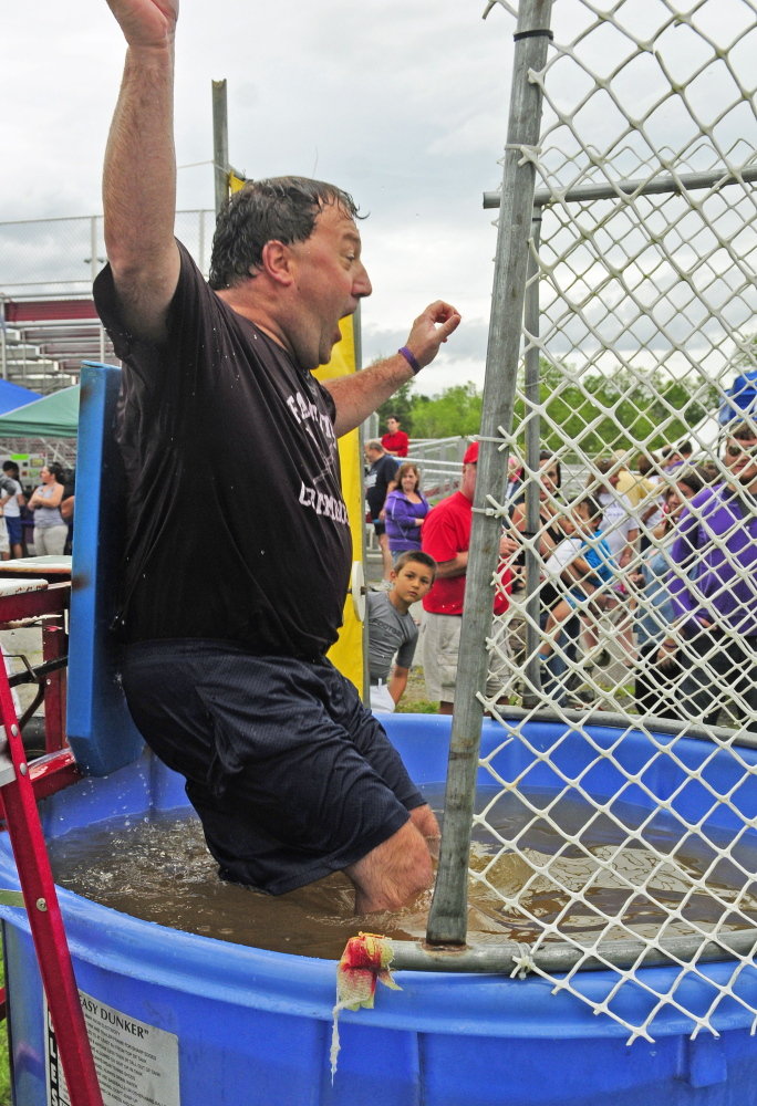 Dave Hopkins hits the dunk tank water when somebody hit the button with a football during a fundraiser on Saturday at Cony High's Alumni Field. Alison Lucas, mother of former Cony quarterback Ben Lucas, was recently diagnosed with cancer.