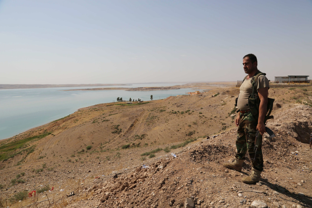 A Kurdish peshmerga fighter stands guard near the Mosul Dam at the town of Chamibarakat outside Mosul, Iraq, Sunday.