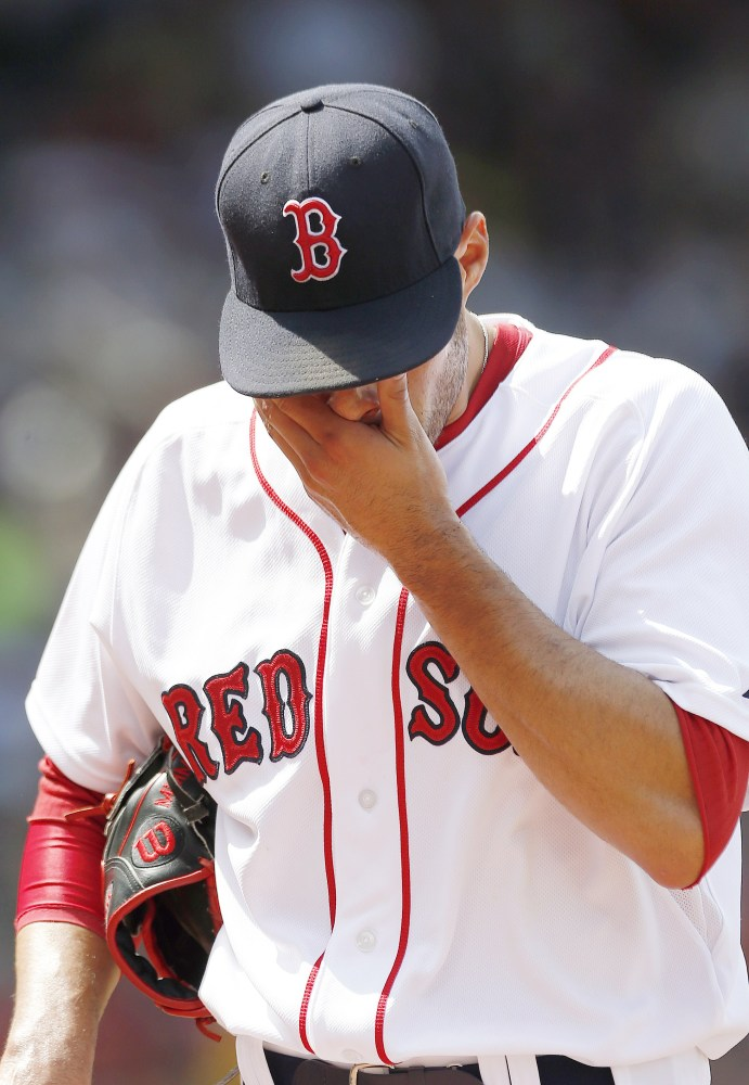 Boston Red Sox's Joe Kelly walks to the dugout after giving up six runs to the Houston Astros during the second inning of a baseball game in Boston, Sunday.