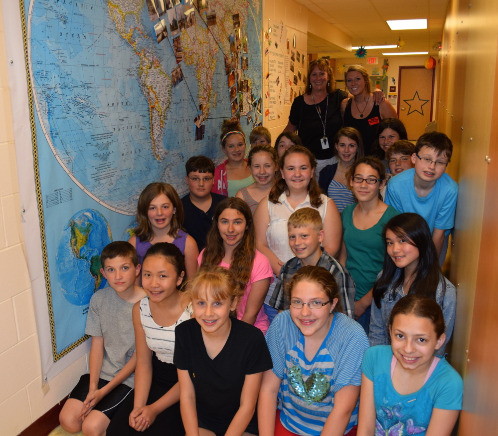 Wells Junior High School sixth-graders meet world traveler and alumna Katie McDonough (rear, right) and Katie's mother, Kim McDonough (rear left), following Katie's eight-month adventure. The group is posing by  a large map in the school hallway, where students marked Katie's travels around the world.