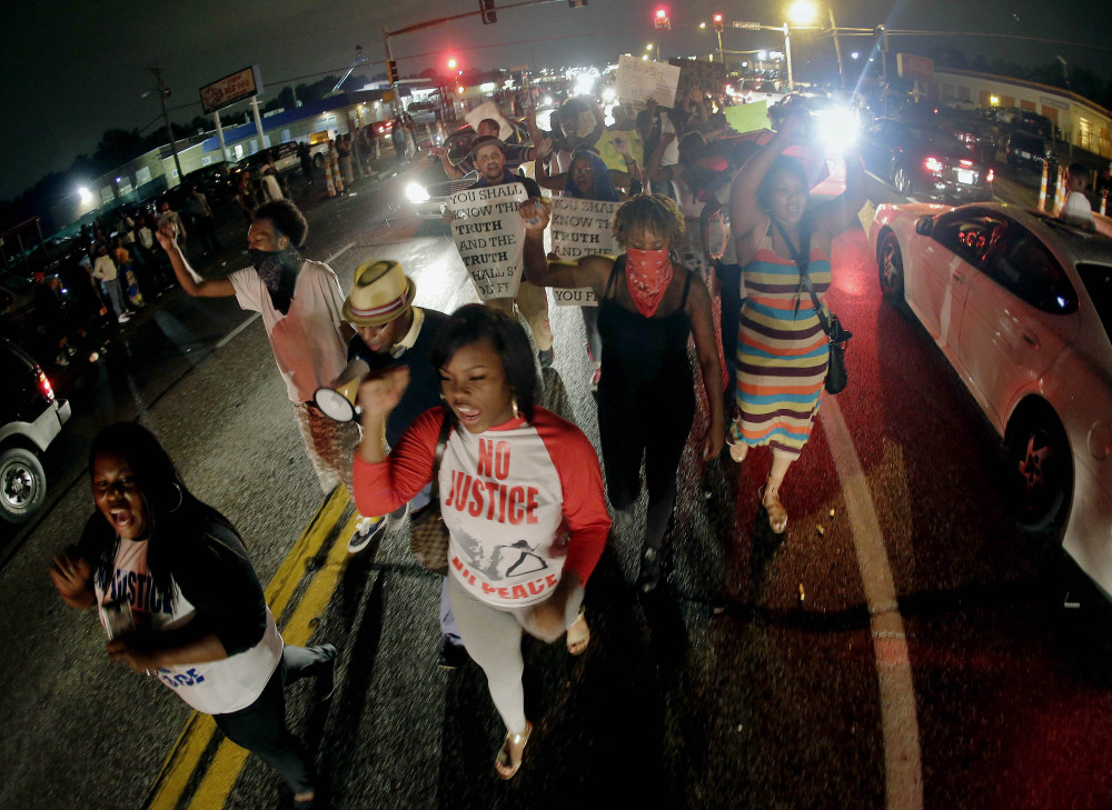 In this Friday, Aug. 15, 2014 file photo, protesters march down the middle of a street in front of a convenience store in Ferguson, Mo. that was looted and burned following the shooting death of Michael Brown, an unarmed black teenager, by a white police officer on Saturday, Aug. 9.