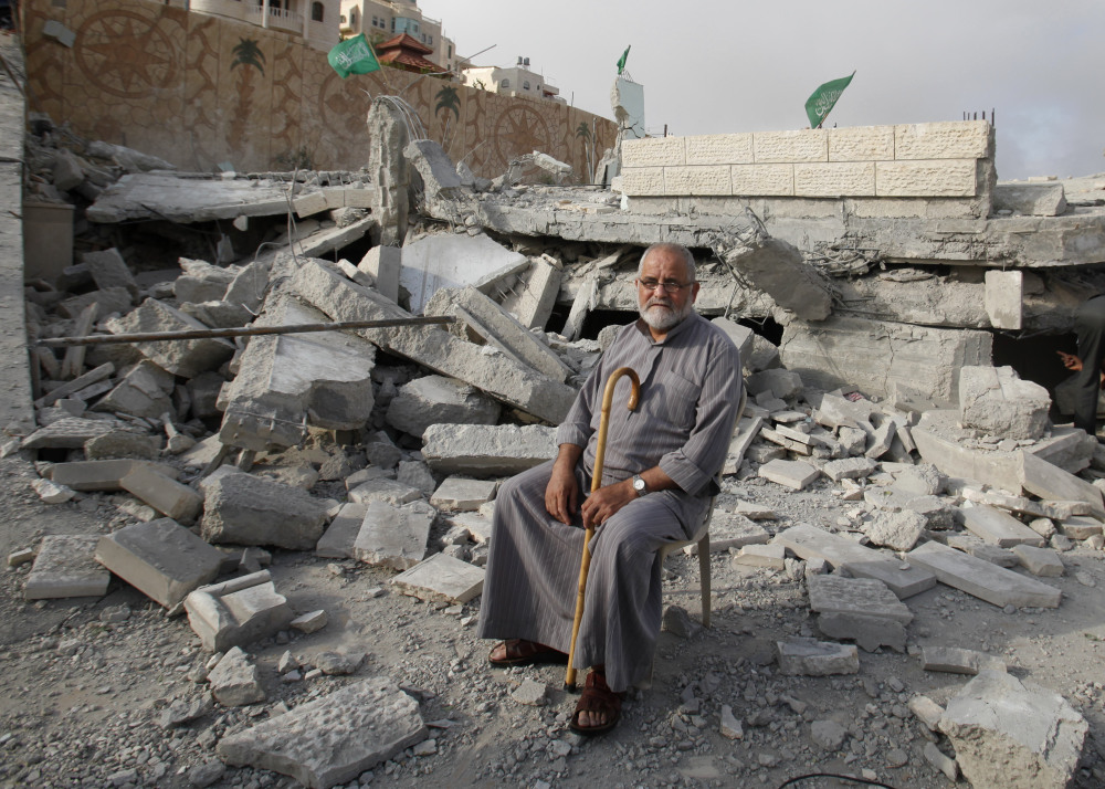 A Palestinian sits in the rubble of the house of Hussam Qawasmeh, one of three Palestinians identified by Israel as suspects in the killing of three Israeli teenagers, after it was demolished by the Israeli army in the West Bank city of Hebron on Monday.
