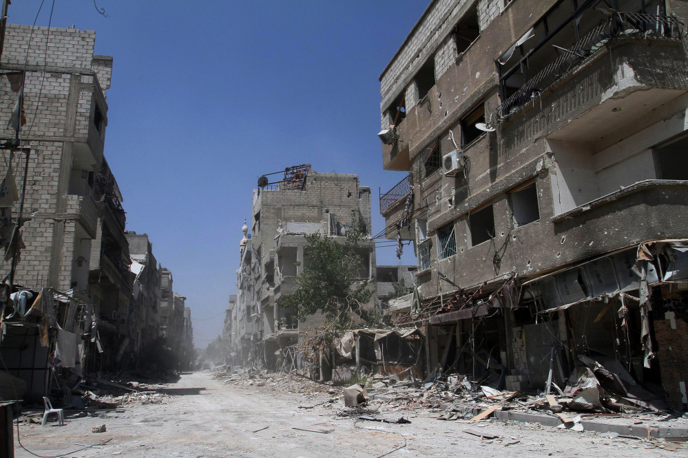 In this photo taken during a Syrian government-led media tour, buildings damaged during battles between Syrian troops and rebels stand along an empty street in Mleiha, some 10 kilometers (6 miles) southeast of downtown Damascus, Syria, Friday.