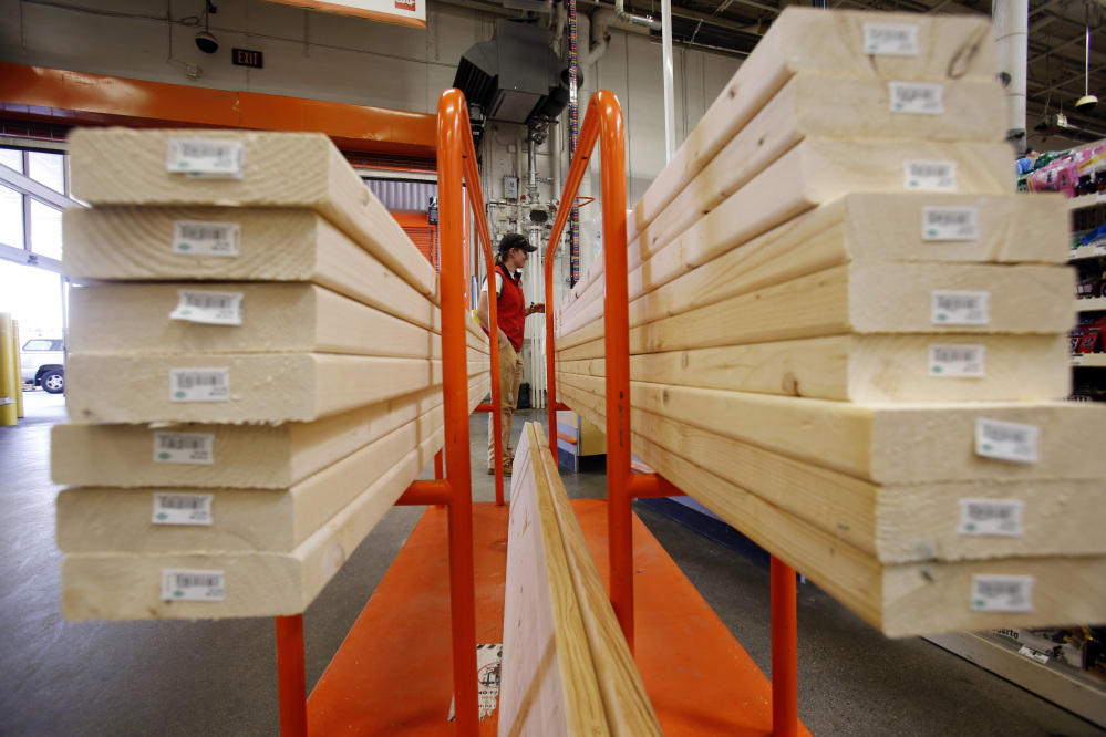 A shopper checks out with her lumber at a Home Depot in Boston in May 2014.