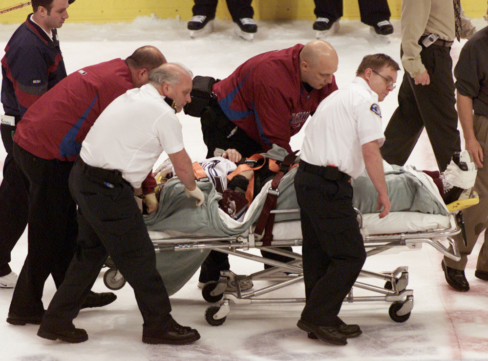 Steve Moore of the Colorado Avalanche is taken off the ice after being hit by the Vancouver Canucks' Todd Bertuzzi on March 8, 2004. A settlement has been reached in Moore's lawsuit against Bertuzzi for his career-ending hit.