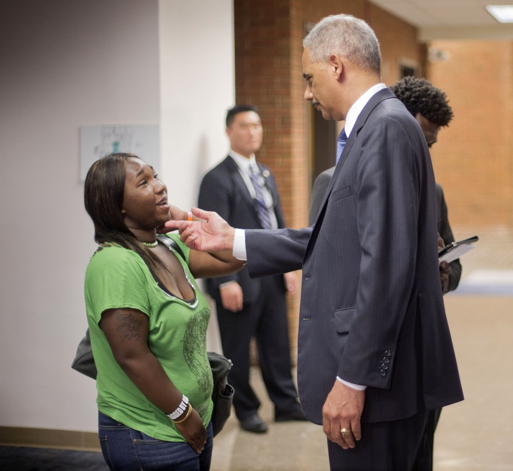 Attorney General Eric Holder talks with Charnell Hurn, 20, a student at St. Louis Community College Florissant Valley, Wednesday in Ferguson, Mo.