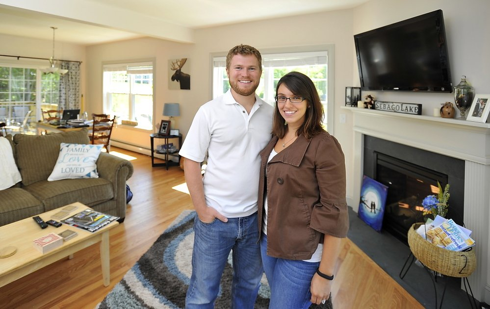 "Rob and Samantha McNamee pose in the home they built in Sebago Heights Estates in Windham. ""Our money goes a lot farther in Maine than in Massachusetts,"" Rob McNamee says."