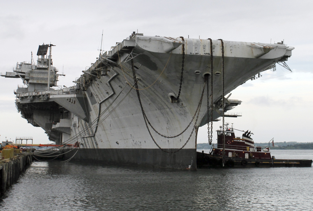 A tug maneuvers alongside the decommissioned aircraft carrier USS Saratoga at Naval Station Newport on Thursday. The ship is making it's final journey to the Esco Marine ship recycling plant in Brownsville, Texas, where it will be scrapped.